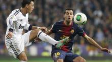 Real Madrid's Mesut Ozil, left, fights for the ball with Barcelona's Sergio Busquets during their Spanish King's Cup semi-final first leg soccer match at Santiago Bernabeu stadium in Madrid, January 30, 2013. (JUAN MEDINA/REUTERS)