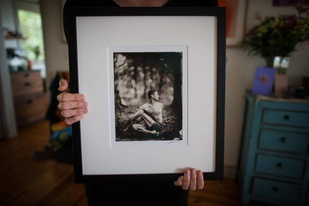Carina Stone holds a photograph of her husband, Michael Stone.