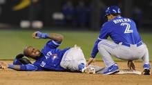 Toronto Blue Jays shortstop Jose Reyes (L) reacts to the pain after hurting his ankle while trying to steal second as third base coach Luis Rivera comes to help in the sixth inning against the Kansas City Royals at their MLB American League baseball game in Kansas City, Missouri April 12, 2013. (DAVE KAUP/REUTERS)