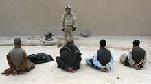 A Canadian soldier guards suspected Taliban prisoners captured in a raid on a compound in northern Kandahar in May, 2006. The suspects were subsequently handed over to the Afghan National Police. (JOHN D MCHUGH/AFP/Getty Images)