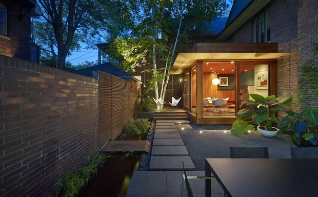 One of the gardens, located to the side, is surrounded by an L-shaped brick wall, making the enclosed area a comfortable outdoor room.