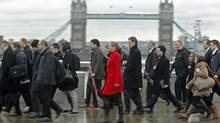 Rush hour workers pass Tower Bridge in the financial district of the City of London January 29, 2013. (Luke Macgregor/REUTERS)