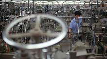 A worker operates machines on a photo and mirror frame assembly line at a factory in Zibo, Shandong Province, in this May 28, 2012 file photo. (ALY SONG/REUTERS)