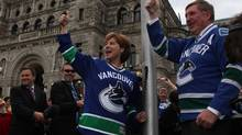 Premier Christy Clark and B.C. Legislative Speaker of the House Bill Barisoff show team support and celebration as they raise the Vancouver Canucks flag before the start of the Stanley Cup Final Tuesday May 31, 2011 in Victoria. (Chad Hipolito For The Globe And Mail/Chad Hipolito For The Globe And Mail)