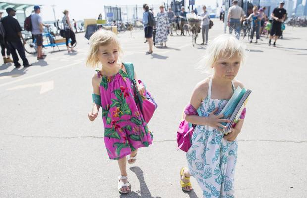 Six-year-old twin sisters Billie Page, right, and Izzy Page, left, walk off the ferry as they temporarily attend Nelson Mandela Park Public School.