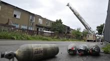 Spent oxygen tanks sit at the scene of a massive townhouse fire that took the life of a young boy in Brampton, Ont., on June 8, 2014. (J.P. MOCZULSKI FOR THE GLOBE AND MAIL)