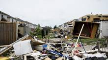 Investigators assess the damage to homes and property in Angus, Ont. on Wednesday, June 18, 2014. Residents of a central Ontario community ravaged by a tornado on Tuesday night are being reunited with their pets while they wait for clearance to return home. THE CANADIAN PRESS/Nathan Denette (Nathan Denette/THE CANADIAN PRESS)