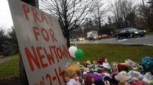 A hearse carrying the casket of of six-year-old Jack Pinto passes a makeshift memorial on its way to Newtown Village Cemetery in Newtown, Conn., Dec. 17, 2012. Jack was one of 20 schoolchildren killed in the Dec. 14 shootings at Sandy Hook Elementary in Newtown. (ERIC THAYER/REUTERS)