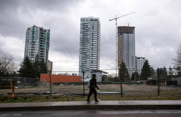 A woman walks by an empty lot behind condo towers in downtown Surrey.