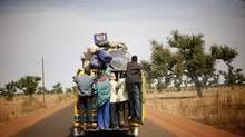 Malians hang on the back of a packed minibus as they drive to Marakala, central Mali, some 240kms (140 miles) from Bamako on Jan. 22, 2013. Thousands of Malians are fleeing their towns, which aid workers say is creating a humanitarian crisis. (Jerome Delay/AP)