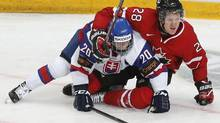 Canada's Griffin Reinhart pins down Slovakia's Martin Reway during the third period of their preliminary round game during the 2013 IIHF U20 World Junior Hockey Championship in Ufa Dec. 28, 2012. (MARK BLINCH/REUTERS)