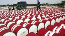 An Indonesian worker walks on barrels of oil at a distribution station of the state-owned oil company Pertamina in Jakarta, Indonesia, in this June 24, 2005 file photo. (AP Photo)
