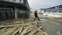 A police officer steps over debris from what's left of the Casino Pier boardwalk three days after Hurricane Sandy came ashore in Seaside Heights, N.J. (STEVE NESIUS/REUTERS)