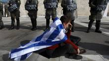 An anti-austerity protester draped with a Greek flag sits in front of police guarding parliament in Athens February 11, 2012 during a demonstration on the second day of a 48-hour strike by Greek workers unions. (YANNIS BEHRAKIS/Reuters)