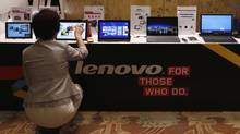 A woman tries a Lenovo tablet on display during a news conference announcing the company's annual results in Hong Kong May 21, 2014. (BOBBY YIP/REUTERS)
