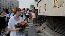 People lay flowers near pictures of the victims of the Malaysian Airlines Flight 17 air crash, in a central square in Kharkiv, Ukraine, Thursday, July 24, 2014. (Sergei Chuzavkov/AP)