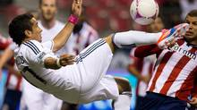 Vancouver Whitecaps' Camilo Sanvezzo, left, of Brazil, attempts a bicycle-kick shot on goal as Chivas USA's Alejandro Moreno, of Venezuela, looks on during the first half of an MLS game in Vancouver, B.C., on Wednesday October 3, 2012. (DARRYL DYCK/THE CANADIAN PRESS)