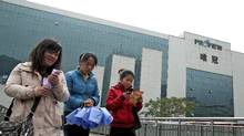In this Feb. 16, 2012 file photo, workers walk on a footbridge outside the Proview Technology office building in Shenzhen, in southern China's Guangdong province. Proview's fortunes may currently be the polar opposite of Apple – one has creditors at the door and the other is the world's most valuable listed company – but both illustrate how the fickle world of technology can make or break a company. (AP/File photo)
