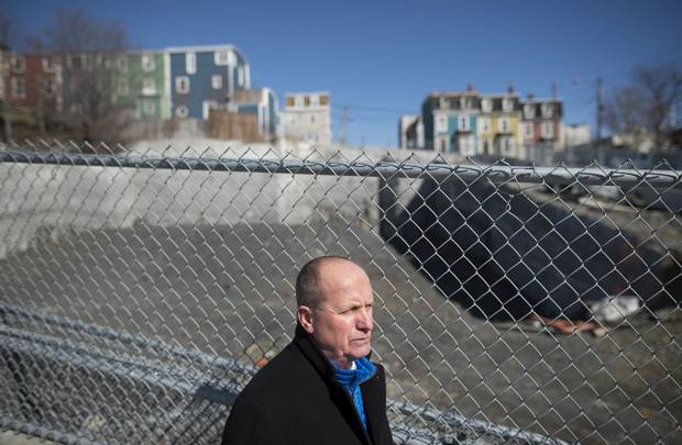 Realtor Larry Hann in front of an idle construction site in downtown St. John's where condos were set for development.