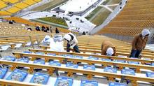 Workers set out seat cushions at Heinz Field in Pittsburgh, Pennsylvania December 27, 2010. The Pittsburgh Penguins will host the Washington Capitals in the 2011 Bridgestone NHL Winter Classic on Saturday. (DAVID DENOMA/REUTERS)