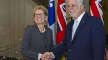 Ontario Premier Kathleen Wynne, left, shakes hands with Quebec Premier Philippe Couillard Thursday, August 21, 2014 at the premier's office in Quebec City. (Clement Allard/THE CANADIAN PRESS)