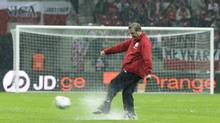England's team manager Roy Hodgson tests the field during heavy rain prior to the World Cup 2014 Group H qualifying soccer match against Poland at the National Stadium in Warsaw, Tuesday, Oct. 16, 2012. (Markus Schreiber/AP)