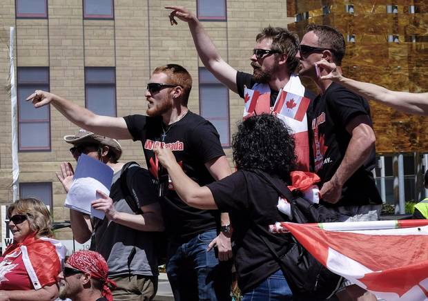 Anti-Islamists shout at counter protesters from behind a police line during an anti-Islam rally in Calgary, Alta., Sunday, June 25, 2017.