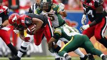 Edmonton Eskimos' Donovan Alexander, right, and Damaso Munoz, tackle Calgary Stampeders' Jon Cornish during first half CFL football action in Calgary, Alta., Monday, Sept. 3, 2012. (Jeff McIntosh/THE CANADIAN PRESS)