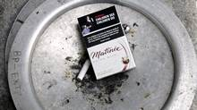 A discarded cigarette pack lies in an ashtray outside an office tower in downtown Toronto February 19, 2007. (J.P. MOCZULSKI)