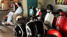 In Islamabad's auto market, Vespas line the garage and showroom belonging to Mohammed Rais (seated). (AFFAN CHOWDHRY FOR THE GLOBE AND MAIL)