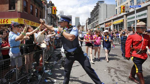 Police officer Keiss Zamir high-fives the crowd at the Gay Pride Parade in Toronto. June 30, 2013.