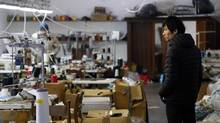 A Chinese immigrant looks on as police officers conduct a check at the Shen Wu textile factory in Prato December 9, 2013. (STEFANO RELLANDINI/REUTERS)