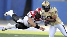 Calgary Stampeders Randy Chevrier (56) dives to tackle Winnipeg Blue Bombers James Johnson (19) on a punt return during Canadian Football League action in Winnipeg, July 10, 2009. (FRED GREENSLADE/REUTERS)
