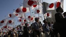 Members of the nationalist movement Ganbare Nippon march with Japanese national flags while paying tribute to the war dead near Yasukuni Shrine in Tokyo. (ISSEI KATO/REUTERS)