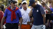 Tiger Woods reacts with fans to his approach shot to the 12th green