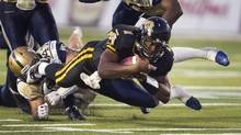 Hamilton Tiger-Cats quarterback Henry Burris (1) dives for a first down despite the efforts of Winnipeg Blue Bombers' Pierre-Luc Labbe to tackle him, late in the fourth quarter of their CFL game in Guelph, Ontario July 13, 2013. (FRED THORNHILL/REUTERS)