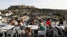 People sit in a cafe of a hotel's roof garden with the Acropolis hill in the background in central Athens August 21, 2013. (JOHN KOLESIDIS/REUTERS)