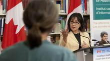 Minister of Health Leona Aglukkaq responds to an inpromptu question on refugee health care from Dr. Megan Williams during an announcement in Ottawa on Wednesday. (Adrian Wyld/THE CANADIAN PRESS)