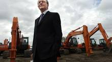 Neil Manning, President and Chief Executive Officer of Wajax Income Fund stands in front of a group of parked large Hitachi excavators at one of the company locations in Milton, Ontario, Canada. (Deborah Baic/The Globe and Mail)