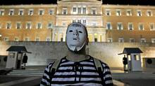 Protesters, dressed as prisoners gather during an event to protest against austerity measures outside the Greek parliament in Athens, Tuesday, Nov. 1, 2011. (Thanassis Stavrakis/AP)