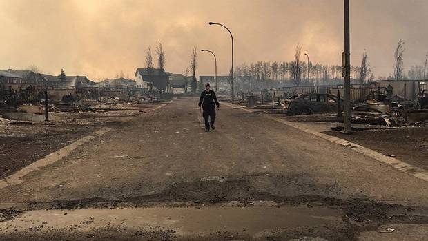 An RCMP officer surveys the damage on a street in Fort McMurray.