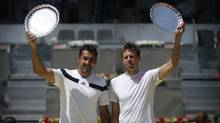 Nenad Zimonjic from Serbia, left, and Daniel Nestor from Canada hold up their trophies after winning the doubles final match against Bob and Mike Bryan from U.S. at Madrid Open tennis tournament in Madrid on May 11. (Daniel Ochoa de Olza/Associated Press)