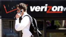 A file photo shows a man speaking on his cell phone as he walks past a Verizon store in Portland, Ore. (Don Ryan/AP)