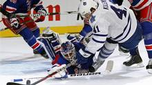 New York Rangers' goalie Henrik Lundqvist (bottom) makes a sprawling save on a shot by Toronto Maple Leafs' Nikolai Kulemin (41) during the second period of their NHL hockey game at Madison Square Garden in New York, October 27, 2011. (MIKE SEGAR/REUTERS)