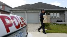 RCMP investigators remove evidence boxes from a home in London, Ontario, Thursday, August 26, 2010. A resident of the house was taken into custody earlier this morning. Police have charged three suspects in what police and court documents say was a terrorism plot that ranged from Canada to Iran, Afghanistan, Dubai and Pakistan. (DAVE CHIDLEY/Dave Chidley/The Canadian Press)