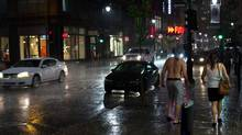 James Lazar photo: July 21, 2011 - A walk In the Montreal rain. While most people sought shelter from the rain, this couple chose to enjoy the reduced traffic on the sidewalk. Serious Montrealers are not deterred from the nightlife by a bit of rain! (James Lazar)