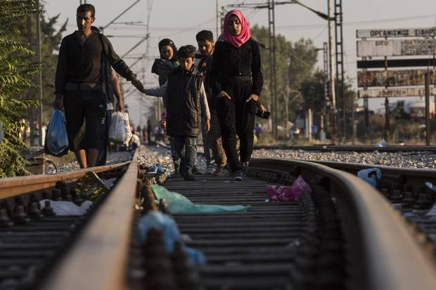 Hundreds of families, mostly Syrian, walk down train tracks towards the Macedonian border to have their papers processed before crossing on Sept. 2, 2015, in Idomeni, Greece.