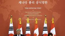 Canadian Prime Minister Stephen Harper, left, answers reporters' question as South Korean President Park Geun-hye listens on during joint press conference after their meeting at the presidential Blue House in Seoul, South Korea, Tuesday, March 11, 2014. (Lee Jin-man/AP)