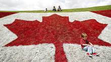 Samuel Rosas celebrates his third birthday (in behind are his cousin Andrea Suarez, aunt Carolina Rosas and father Camilo Rosas), by playing on a giant Canada Flag painted on a hillside at a Canada Day celebration, Wednesday, July 1, 2009, in London, Ontario. Samuel's family came to Canada from Columbia 3 1/2 years ago.________THE CANADIAN PRESS/Dave Chidley (DAVE CHIDLEY/The Canadian Press)