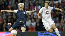 United States' Megan Rapinoe, left, prepares to kick the ball against Canada's Christine Sinclair, right, during their semi-final women's soccer match at the 2012 London Summer Olympics, in Manchester, England, Monday, Aug. 6, 2012. (Associated Press)